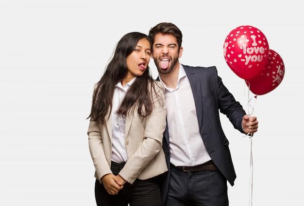 バレンタインデーおかしなとフレンドリーな示す舌で若いカップル