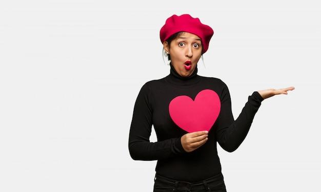 手のひらに何かを保持しているバレンタインデーの若い女性