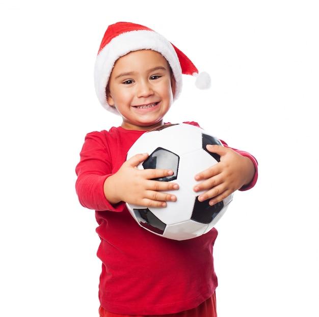 子供は笑顔で彼のボールを保持します