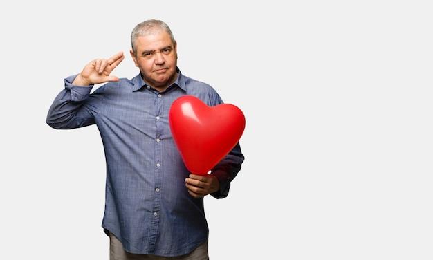 自殺ジェスチャーをやっているバレンタインデーを祝う中年の男