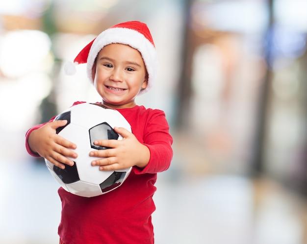 ぼやけた背景を持つ彼のボールを持ってポーズをとって幸せな子供
