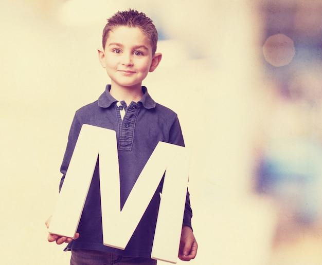 Симпатичный мальчик показывая букву м