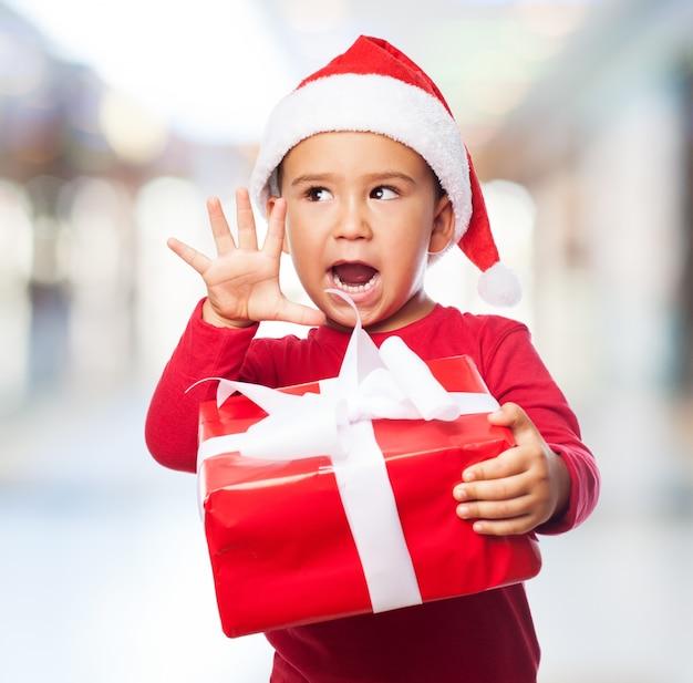 表情豊かな少年は白い弓で贈り物を保持します