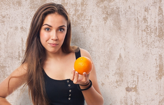 Женщина с оранжевом в руке