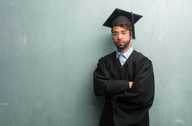 彼の腕を交差、真剣で印象的な、自信を持って力を示すコピースペースを持つグランジ壁に対して若い卒業男