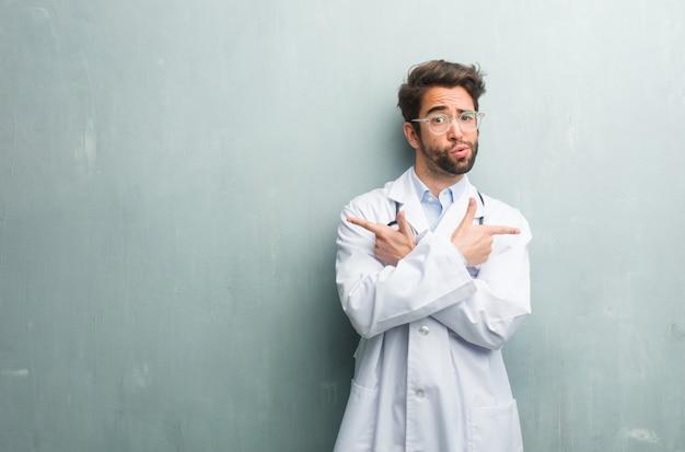コピースペースとグランジ壁に対して若いフレンドリーな医者男混乱して疑わしい