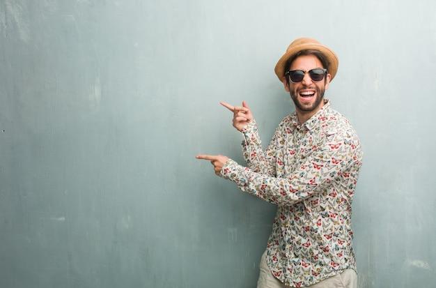 側を指しているカラフルなシャツを着ている若い旅行者男性