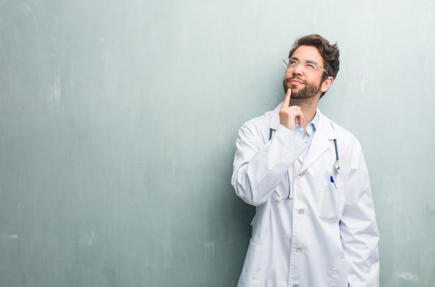 考えを見上げて、考えについて混乱しているコピースペースを持つグランジ壁に対して若いフレンドリーな医者男は、解決策を見つけることを試みているでしょう
