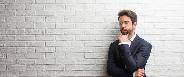 考えを探して、考えについて混乱している若いフレンドリーなビジネスマンは、解決策を見つけようとしているでしょう