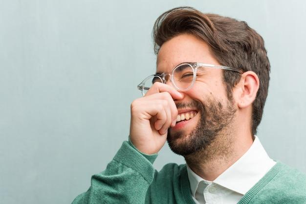 笑って、楽しんで、リラックスして陽気で、ハンサムな起業家の若者の顔のクローズアップ