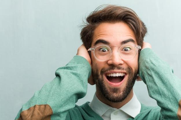若いハンサムな起業家の男性の顔のクローズアップの驚きとショックを受けました