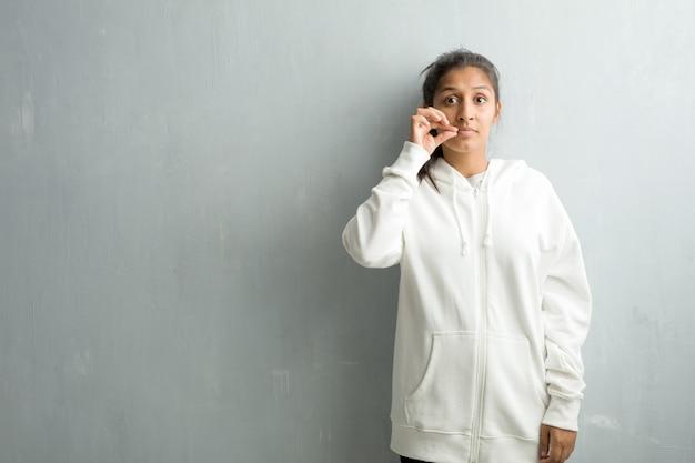 秘密を守るか沈黙、深刻な顔、服従の概念を求めてジムの壁に対してスポーティなインドの若い女性