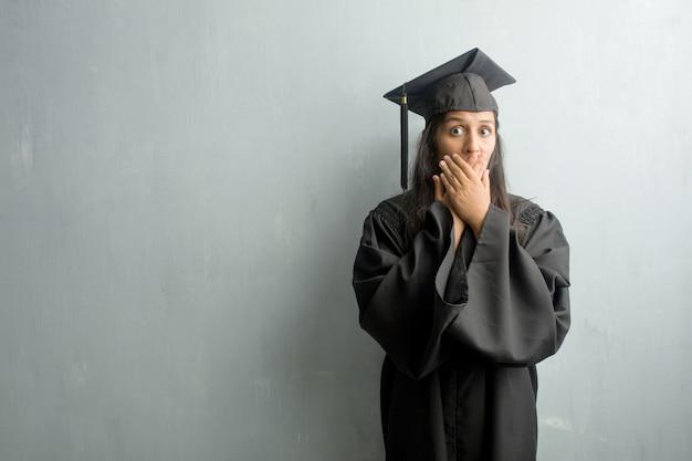 口を覆っている壁に対して若い卒業インドの女性
