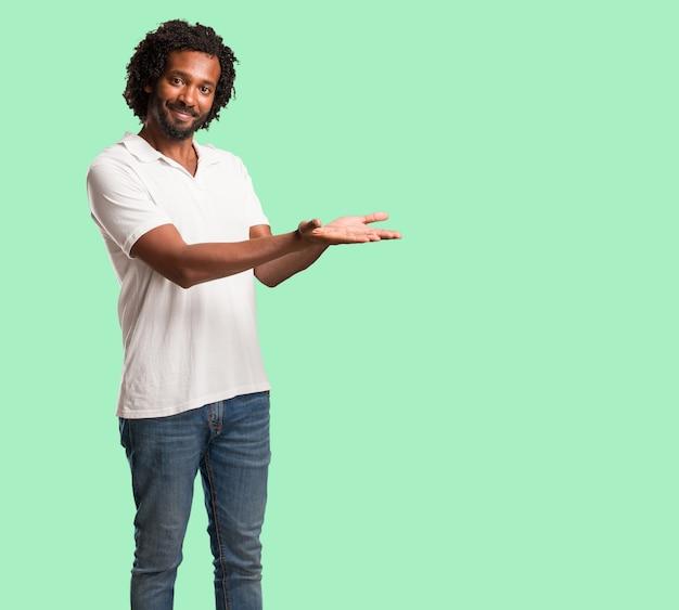 ハンサムなアフリカ系アメリカ人の手で何かを保持している、製品を見せて、笑顔で陽気、想像上のオブジェクトを提供する