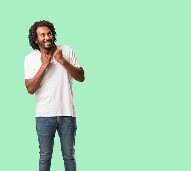 ハンサムなアフリカ系アメリカ人はとても幸せで興奮して、腕を上げて、勝利または成功を祝って、宝くじに勝ちます