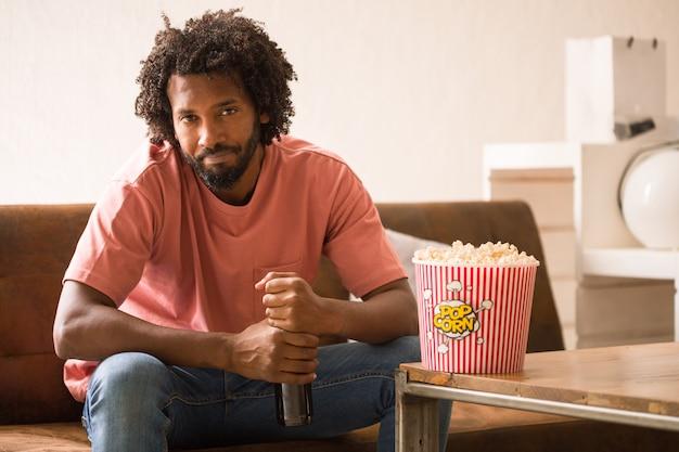Молодой африканский человек смотря кино держа ведро попкорна и выпивая пиво.