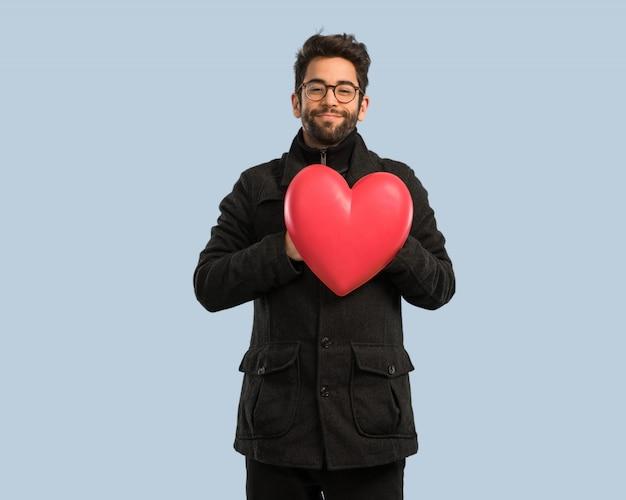 心臓の形を保持している若い男