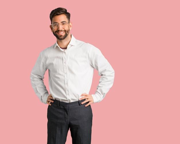 Молодой красивый деловой человек с руки на бедрах