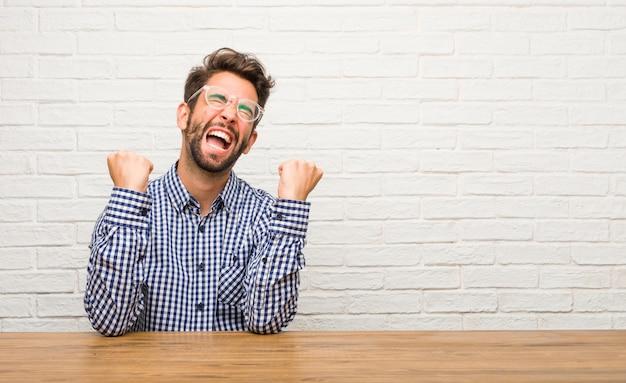 白人の若者が非常に幸せで興奮して座って腕を上げる、勝利または成功を祝う、宝くじ