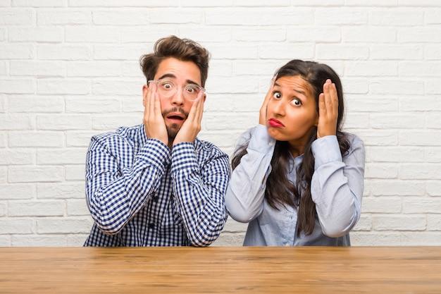 若いインド人女性と白人男性カップルの欲求不満と絶望的な怒っていると頭の上の手で悲しい
