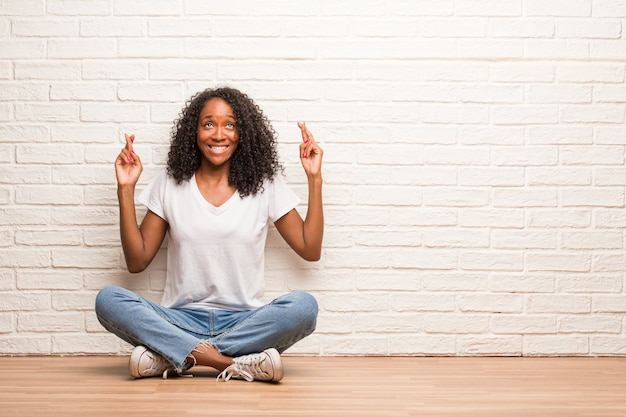 彼の指を交差する木の床の上に座っている若い黒人女性は、将来のプロジェクト、興奮しているが心配している、緊張した表情で目を閉じてラッキーになりたいです。