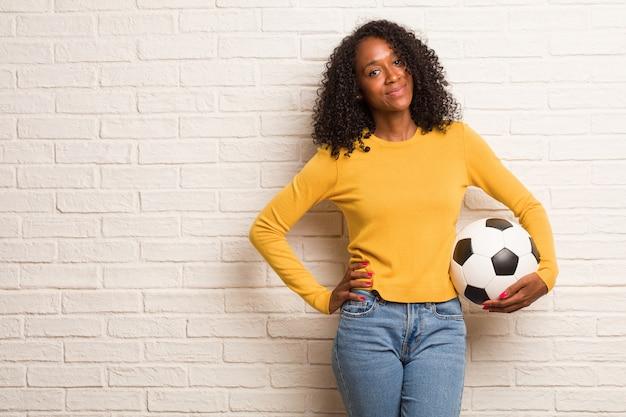 立って、リラックスして笑顔、非常に肯定的で陽気な腰に手を持つ若い黒人女性