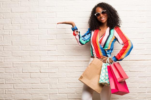 Молодая негритянка держит что-то руками, показывает продукт, улыбается и веселится, предлагая воображаемый предмет