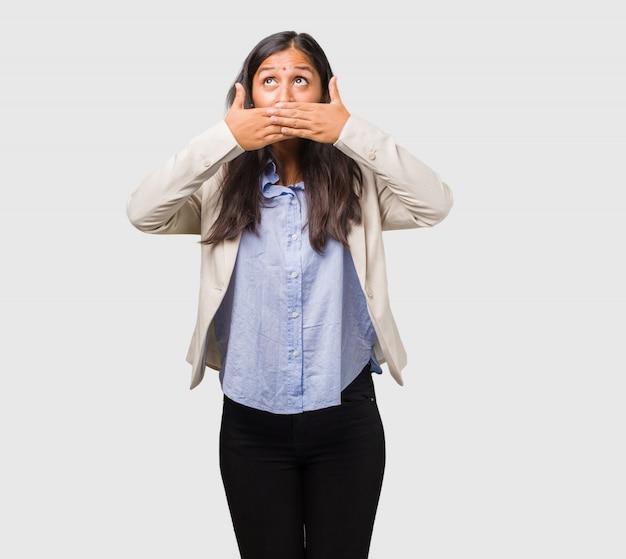 口を覆っている若いビジネスインド人女性
