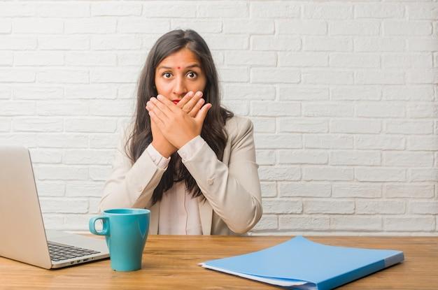 何も言わないようにしようとしている口、沈黙と抑圧の象徴をカバーするオフィスで若いインド人女性