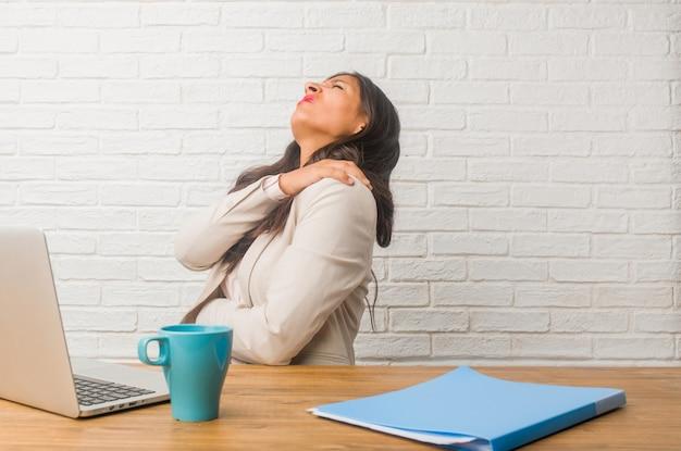 仕事のストレス、疲れて鋭いため背中の痛みを持つオフィスで若いインド人女性