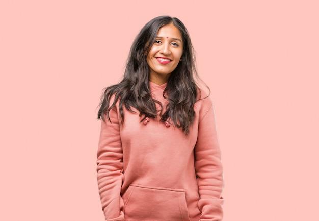 陽気で大きな笑顔、自信を持って、フレンドリーで誠実、積極性と成功を表現するフィットネス若いインド人女性の肖像画