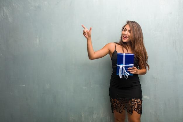 側を指している壁に対してドレスを着ている若いきれいな女性の肖像画