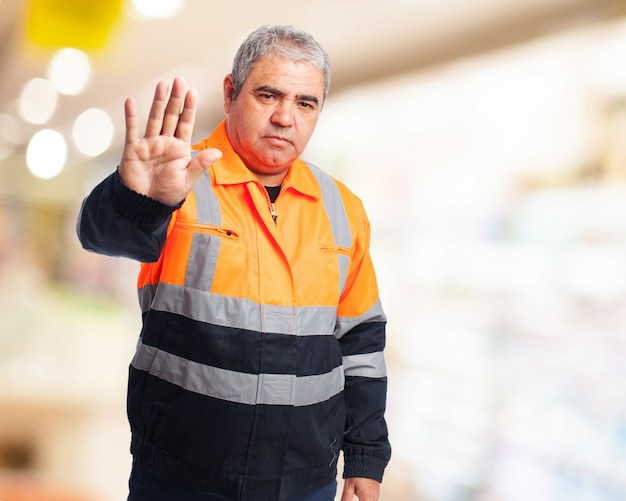 「停止」を作るオレンジ作業ツナギを持つ男