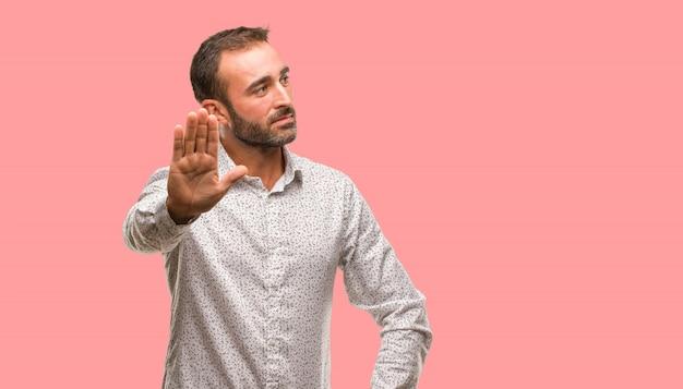 Кавказский мужчина на сером фоне, кладя руку впереди