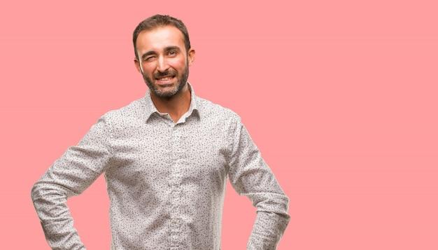 Кавказский мужчина на сером фоне водорослей, веселый, дружелюбный и беззаботный жест