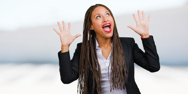 Портрет молодой чернокожей деловой женщины, кричащей счастливой, удивленной предложением или повышением по службе, зияющей, прыгающей и гордой
