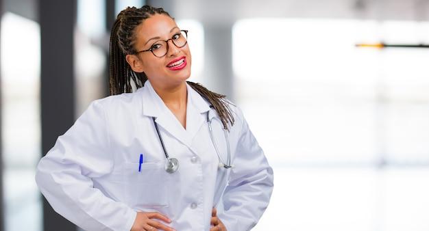 Портрет молодой женщины чернокожего доктора с руками на бедрах, стоя, расслабленный и улыбающийся, очень позитивный и веселый