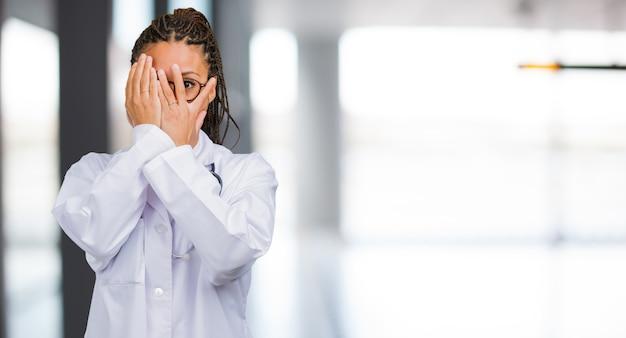 若い黒人医師の女性の肖像画は心配して怖い感じ、顔を見て、カバー、恐怖と不安の概念