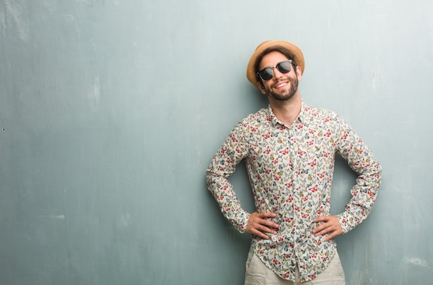 Молодой путешественник человек, одетый в красочную рубашку с руки на бедрах, стоял, расслабился и улыбался