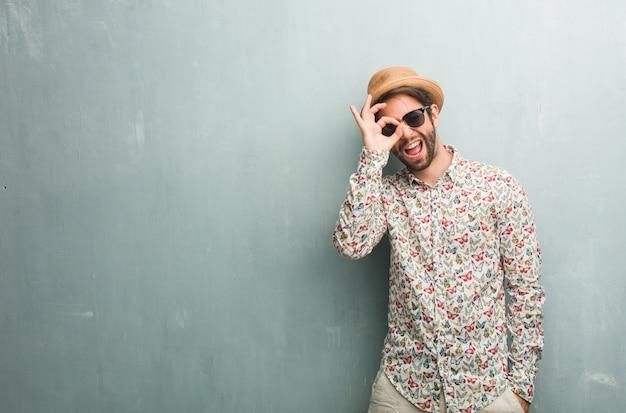 Молодой путешественник человек, одетый в красочную рубашку, веселый и уверенный делает хорошо жест
