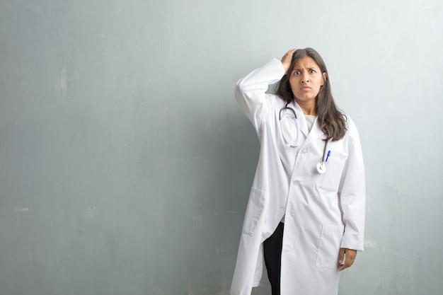 心配し、圧倒された、忘れなやかな、壁に対する若いインド人医師女性