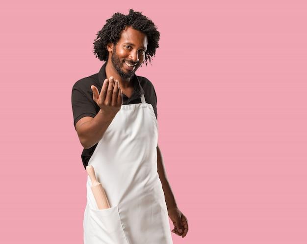 ハンサムなアフリカ系アメリカ人のパン屋、自信を持って来て招待して、手でジェスチャーを作る、前向きでフレンドリー