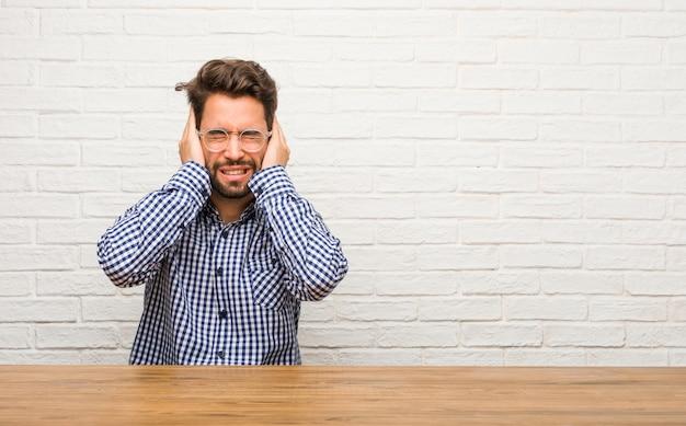 怒っているといくつかの音を聞くのはうんざりして座って手で耳を覆っている若い白人男性