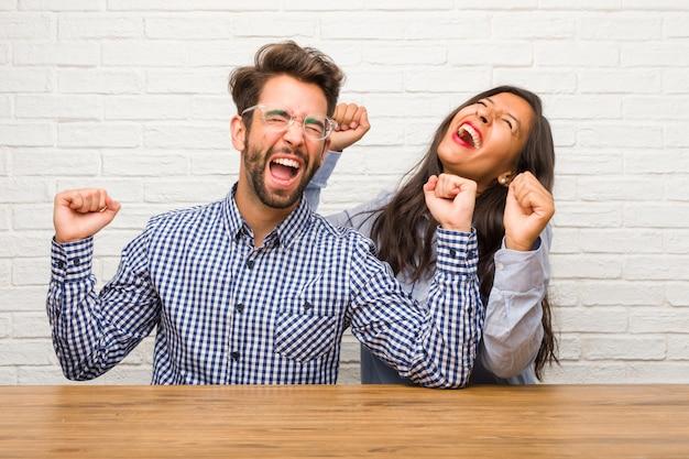 若いインド人女性と白人男性のカップルは非常に幸せで興奮して、腕を上げる、勝利または成功を祝う、宝くじを獲得