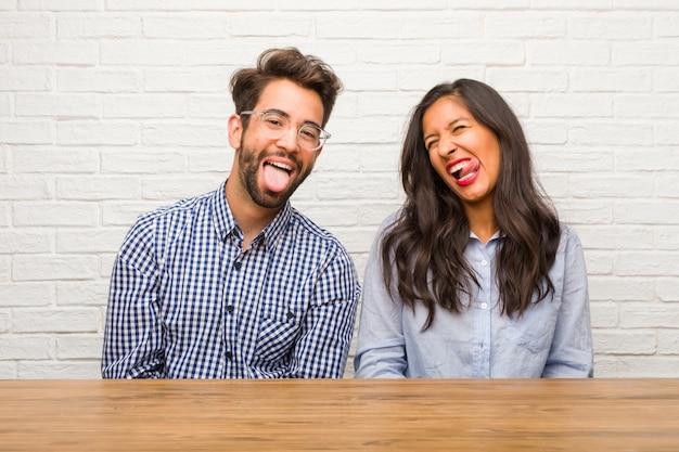 遊びや楽しみのしるしとして舌を見せて自信と感情、楽しさとフレンドリー、若いインド人女性と白人男性カップル