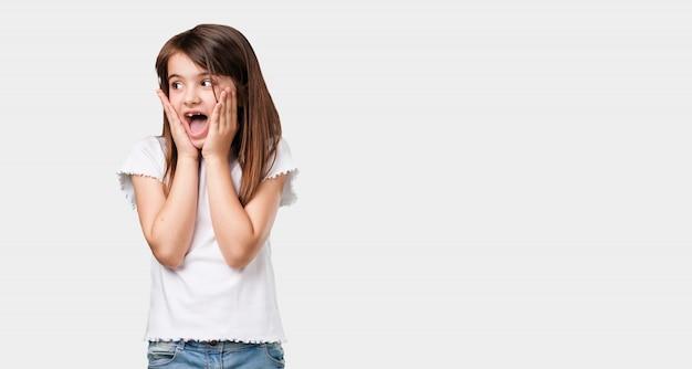 全身の小さな女の子が驚きとショックを受けて、広い目で見て、オファーや新しい仕事に興奮して、コンセプトに勝つ