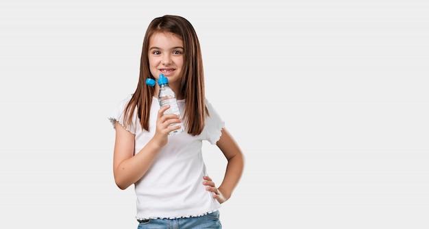 Полное тело маленькой девочки улыбается, довольный, держит бутылку холодной воды, вспоминая, что гидратация важна для организма.