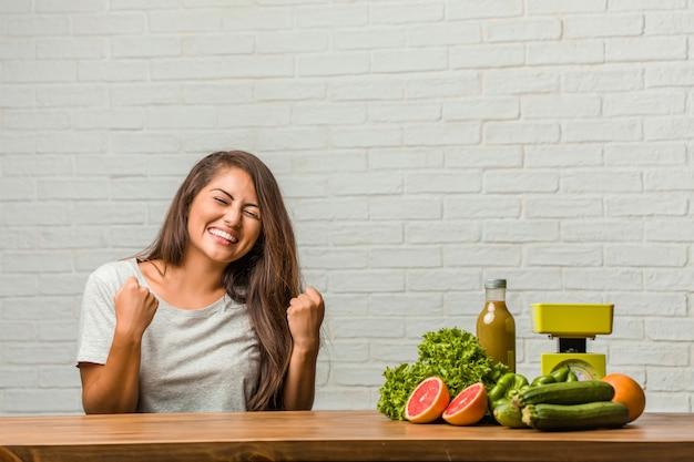 ダイエットの概念非常に幸せで興奮して、腕を上げる、勝利または成功を祝う、宝くじに当たる健康的な若いラテン女性の肖像画
