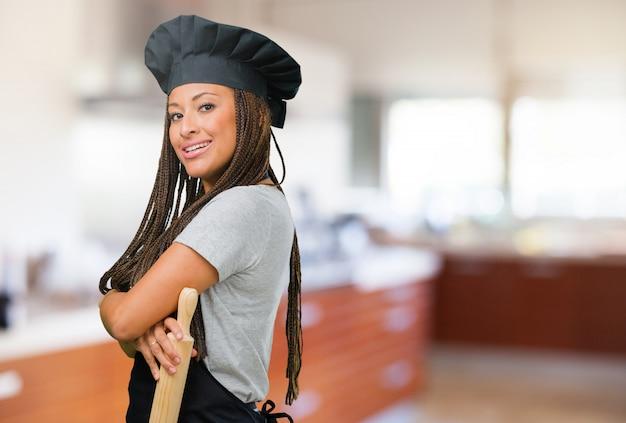 Портрет молодой женщины чернокожего пекаря, скрещивающей руки, улыбающейся и счастливой, уверенной и дружелюбной
