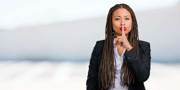 Портрет молодой черной деловой женщины, держащей в секрете или просящей молчание, серьезное лицо, концепцию послушания